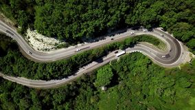 Top down view from above view of a curved winding road trough the mountains stock video footage