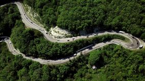 Fly over curved winding road trough the mountains stock video