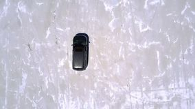 Top view aerial drone shot of silver minivan car driving along incredible salt lake desert plain with amazing texture. Camera follows modern vehicle moving on stock video footage