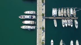 Top view aerial footage of Porto Montenegro marina pier with car moving among luxury yachts and sailboats. Top view aerial footage of Porto Montenegro Tivat stock video