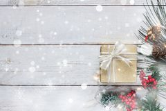 Top view aerial image of merry Christmas & Happy new year concept. Snowflakes fall on gold gift box with essential items on modern rustic wooden white Royalty Free Stock Images