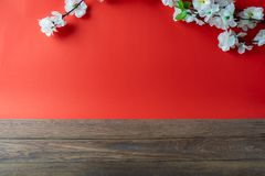 Top view aerial image shot of arrangement decoration Chinese new year & lunar new year holiday background concept. White cheery blossom on red paper and brown stock photo