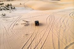 Top view aerial photo from flying drone of a professional driver having dangerous ride with car in desert landscape. Active. Extreme sport leisure with stock photography