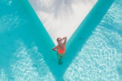 Top view aerial photo of model in bright swimwear relaxing in hotel pool during her summer weekend. Top view aerial photo from flying drone of a seductive sexy stock images