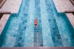 Top view aerial photo of a seductive sexy model in white swimwear is enjoying relax in hotel pool during her summer Stock Image