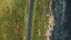 Top view aerial tracking shot of black car driving along atmospheric autumn coastline road, beautiful eroded sea shore