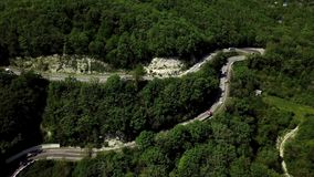 Aerial view of a curved winding road trough the mountains stock video