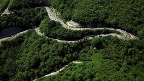 Aerial view of a curved winding road with cars passing stock footage