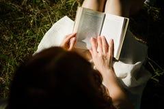 Top view af young girl enjoying book outdoors, Royalty Free Stock Photos
