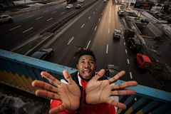 Top view of afro-amercan man rising his hands up and screaming. On the background of the city road Stock Photos