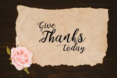 Top view of aged paper with give thanks today lettering and rose flower. On wooden table Stock Photos