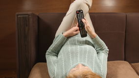 TOP VIEW: Aged woman change a TV channels by remote on a sofa at home stock footage