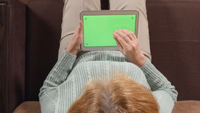 TOP VIEW: Aged woman with a tablet PC green screen on a sofa - close up. TOP VIEW: Aged woman with tablet PC green screen on a sofa - close up stock video footage