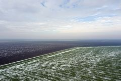 Top view of agricultural green and brown fields Spring. Top view of agricultural green and brown fields covered with snow Royalty Free Stock Images