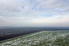 Top view of agricultural green and brown fields Spring. Top view of agricultural green and brown fields covered with snow Stock Images