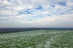 Top view of agricultural green and brown fields Winter. Top view of agricultural green and brown fields covered with snow Royalty Free Stock Photography