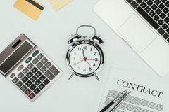 Top view of alarm clock, calculator, contract with pens, credit card and laptop. On white Royalty Free Stock Photo