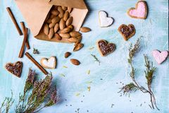 Top view of almonds, heart shaped cookies, cinnamon sticks and green branches with flowers Royalty Free Stock Photos