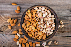 Top view of almonds and pistachios on a wooden bowl Stock Images