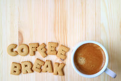 Top view of alphabet shaped biscuits, spelling the word COFFEE BREAK and a cup of coffee on wooden table. With free space for text and design Royalty Free Stock Photo