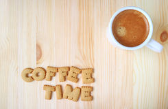 Top view of alphabet shaped biscuits, spelling the word COFFEE TIME and a cup of coffee on wooden table. With free space for text and design Royalty Free Stock Photos