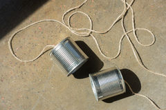 Top view of aluminium tin cans connected with rope on the ground. Tin cans telephone Stock Photography