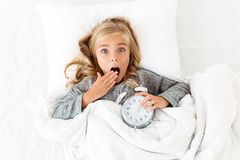 Top view of amazed blonde girl covering her mouth with hand, lyi Royalty Free Stock Image