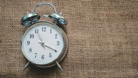 Top- view analog clock table on sack background , vintage style Stock Image