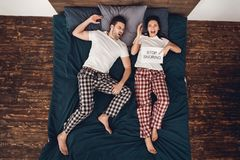 Top view. Annoyed adult woman holds sheet in his hand where it says stop snoring. Top view. Annoyed adult women holds sheet in his hand where it says stop Stock Photography