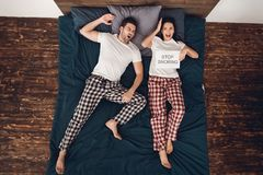 Top view. Annoyed adult woman holds sheet in his hand where it says stop snoring. Top view. Annoyed adult women holds sheet in his hand where it says stop Royalty Free Stock Images