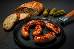 Top view appetizing ruddy juicy sausages fried in large frying pan. Served with sliced rye bread and three pickled cucumbers on black background stock image