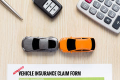 Top view of approved vehicle insurance claim form with car toy c. Rash on wooden desk concept Royalty Free Stock Photos
