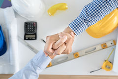 Top view Architect and engineer shaking hands, finishing up a me Royalty Free Stock Image