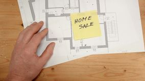 Top view, an architect`s hand rests a yellow post it with written home sale, ideal footage for topics such as building. Renovation, design, new home and family stock video footage