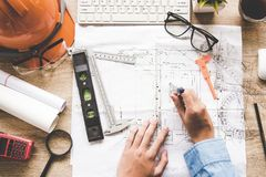 Top View Architect working on blueprint. Architects workplace.  Engineer tools and safety control,. Blueprints, ruler, orange helmet,radio,laptop and divider Stock Photography
