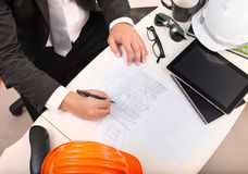 top view of architect working table with drawing perspective building plan and sunglasses ,safety helmet stock photo