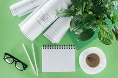 Top view of architect workplace with empty textbook blueprints coffee and plant. On table royalty free stock image