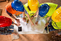 Top view of architects check blue print if construction is going. Top view of group of architects and engineers checking blue print if construction is going as Stock Photos