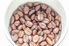 Top view of aroma coffee beans in paper cup. Top view and close up texture of roasted aroma coffee beans in paper cup with natural sunlight Royalty Free Stock Photography