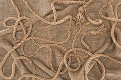 Top view of arranged brown nautical rope with knots. On sackcloth stock photo