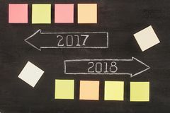 Top view of arranged empty sticky notes and arrows with 2017, 2018 year signs on dark. Wooden surface stock illustration