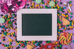 Top view of arranged masquerade masks, candies, cookies and empty blackboard. On purple royalty free stock photo