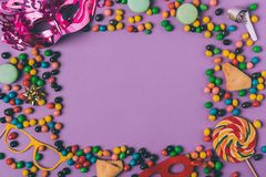 Top view of arranged masquerade masks, candies and cookies. On purple royalty free stock photo