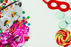 Top view of arranged masquerade masks, macarons and candies. On grey, purim holiday concept stock image