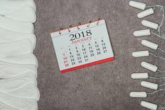 Arranged menstrual pads, tampons and calendar on grey surface. Top view of arranged menstrual pads, tampons and calendar on grey surface stock images