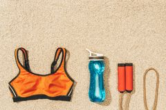 Top view of arranged sportswear, skipping rope and water bottle on sand royalty free stock image