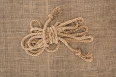 Top view of arranged tied brown nautical rope. On sackcloth stock images