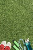 Top view of arranged water bottle, jump rope and sneakers. On green grass royalty free stock photos