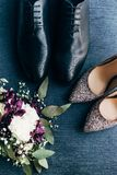 Top view of arranged wedding bouquet, bridal and grooms shoes. On blue background royalty free stock photos