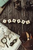 Top view of arranged wooden blocks in travel word with map, retro photo camera, bag and magnifying glass on dark. Wooden tabletop royalty free stock images